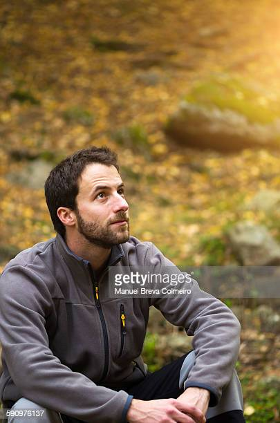 Carefree man seated in the woods