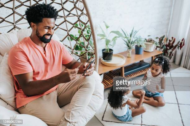 carefree man smiling holding smartphone and credit card in hand making consultation on internet banking and daughters playing in the living room of the house. - brazil stock pictures, royalty-free photos & images