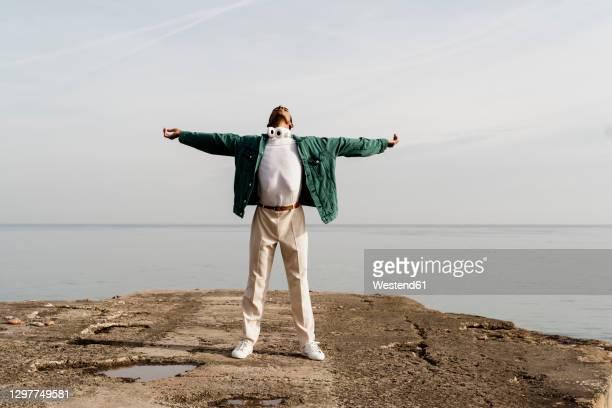 carefree man with arms outstretched against sea on pier - les bras écartés photos et images de collection