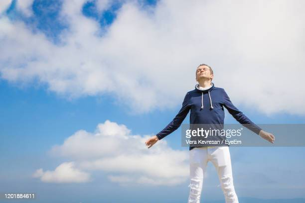 carefree man with arms outstretched enjoying in freedom against the sky. copy space. - 息を止める ストックフォトと画像