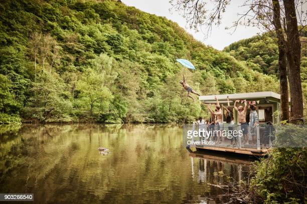 carefree man with family and friends jumping from houseboat in the water - houseboat stock pictures, royalty-free photos & images