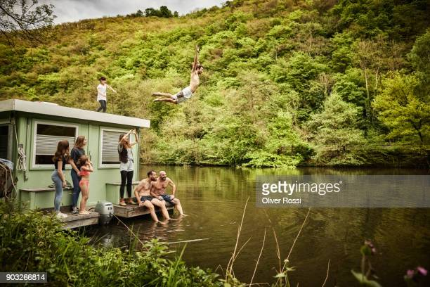 carefree man with family and friends jumping from houseboat in the water - ecoturismo foto e immagini stock
