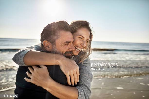 carefree mature man and woman hugging at the sea - love stock pictures, royalty-free photos & images