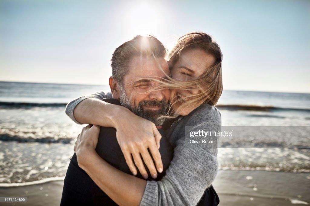 Carefree mature man and woman hugging at the sea : Foto de stock