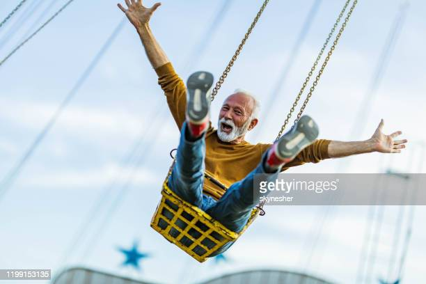 carefree mature man having fun on chain swing ride in amusement park. - freedom stock pictures, royalty-free photos & images