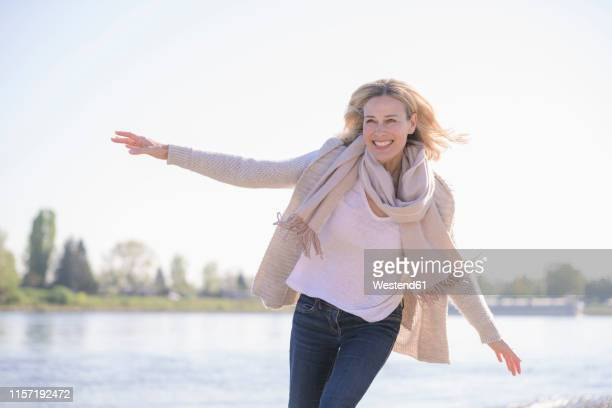 carefree mature woman at the riverside - vitalität stock-fotos und bilder
