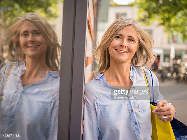 Sorglose Reife Frau neben einem retail store window