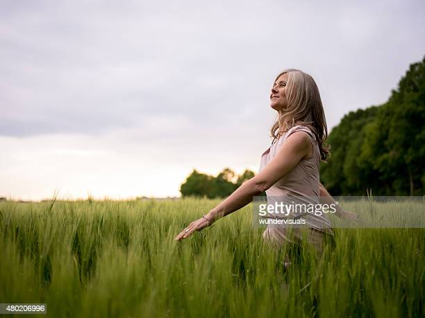 Carefree mature woman walking through a summer park