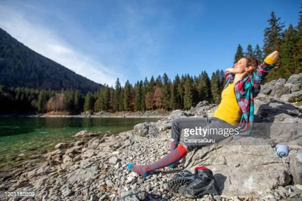 湖畔でリラックスできる気ままなミッドアダルト女性 - ストック写真 - 30代の女性だけ ストックフォトと画像