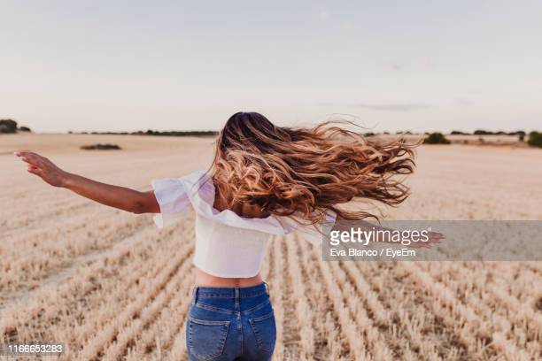 carefree mid adult woman with arms outstretched standing on agricultural field - femme brune de dos photos et images de collection