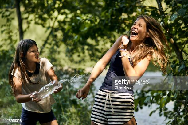 carefree mother and daughter splashing with water bottle in summer - women in wet t shirts stock pictures, royalty-free photos & images