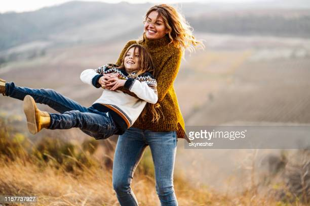 carefree mother spinning her daughter in autumn day on a afield. - autumn stock pictures, royalty-free photos & images