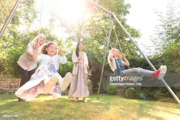 Carefree multi-generation women swinging in backyard