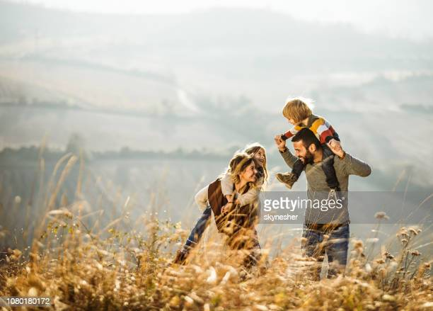 carefree parents having fun with their kids on a field. - familia imagens e fotografias de stock