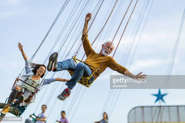 carefree people having fun on chain swing ride in amusement park. - active lifestyle stock pictures, royalty-free photos & images