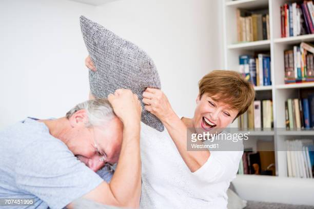 carefree senior couple at home having a pillow fight - naughty wife stock photos and pictures