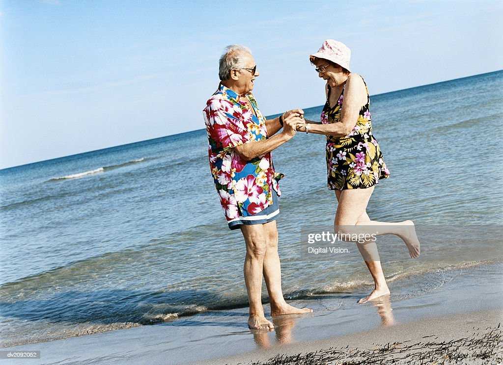Carefree Senior Couple Dance on the Beach at the Water's Edge : Stock Photo