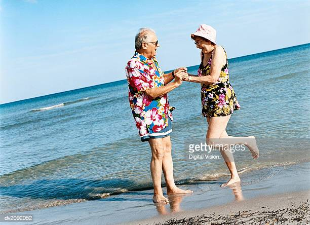 Carefree Senior Couple Dance on the Beach at the Water's Edge
