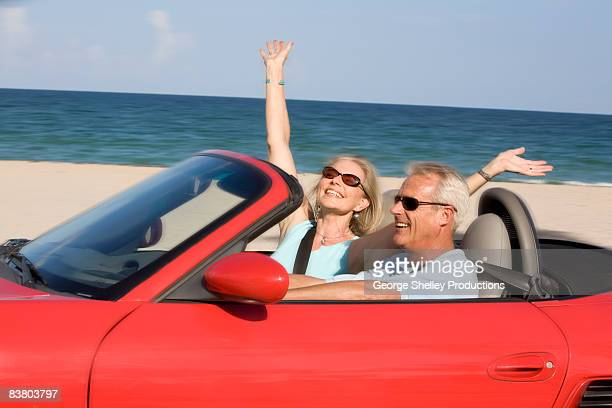 carefree senior couple in a red convertible - celebration fl stock pictures, royalty-free photos & images