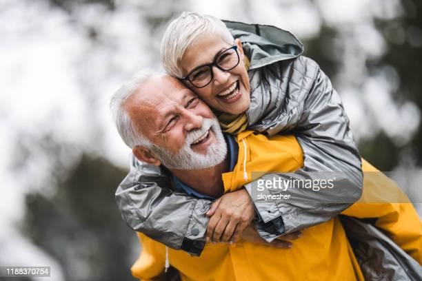 couples aînés insouciants dans des imperméables piggybacking dans la nature. - senior dynamique photos et images de collection