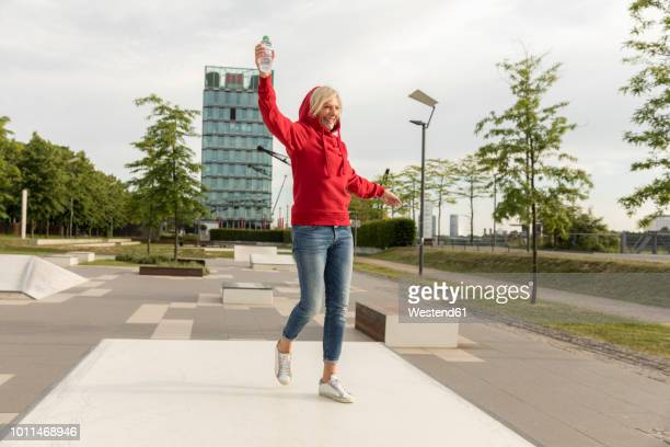 carefree senior woman wearing red hoodie outdoors - red jacket stock pictures, royalty-free photos & images