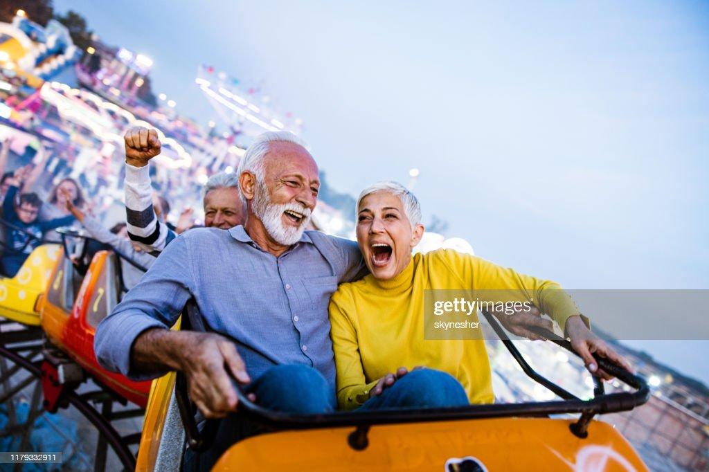 Carefree seniors having fun on rollercoaster at amusement park. : Stock Photo