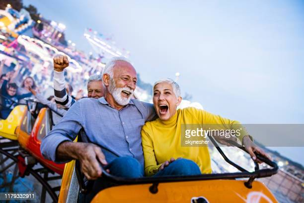 carefree seniors having fun on rollercoaster at amusement park. - traveling carnival stock pictures, royalty-free photos & images