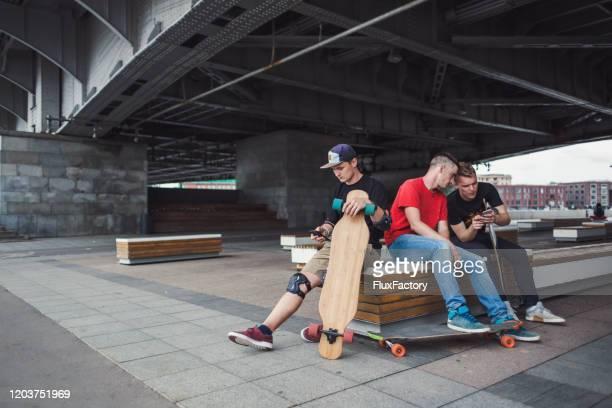 zorgeloze schaatser die mobiele telefoon gebruikt - skateboardpark stockfoto's en -beelden