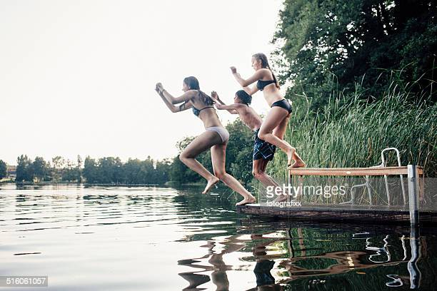 carefree summer day: teenagers jumping into a lake