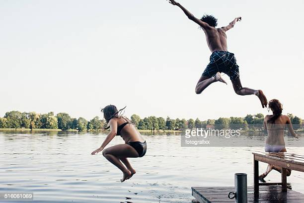 carefree summer day: young adults jumping into a lake
