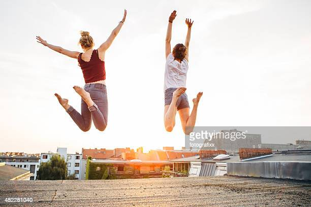 carefree summer: rear view of jumping teenage girls on roof
