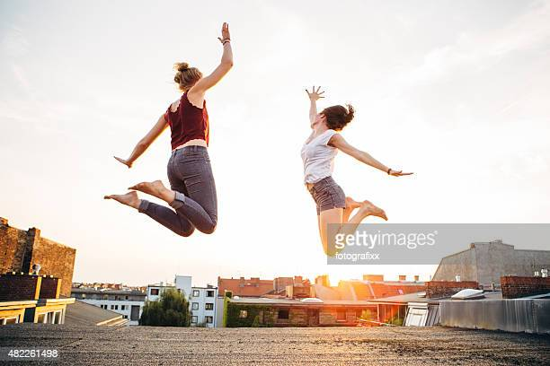 carefree summer: rear view of jumping women on a roof