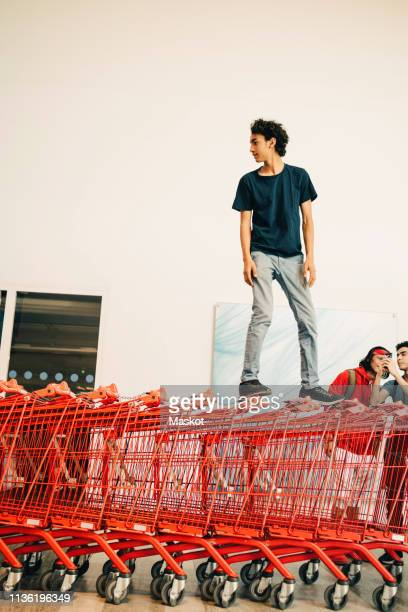 carefree teenage boy standing on stacked red shopping carts outside mall - thème de la photographie photos et images de collection