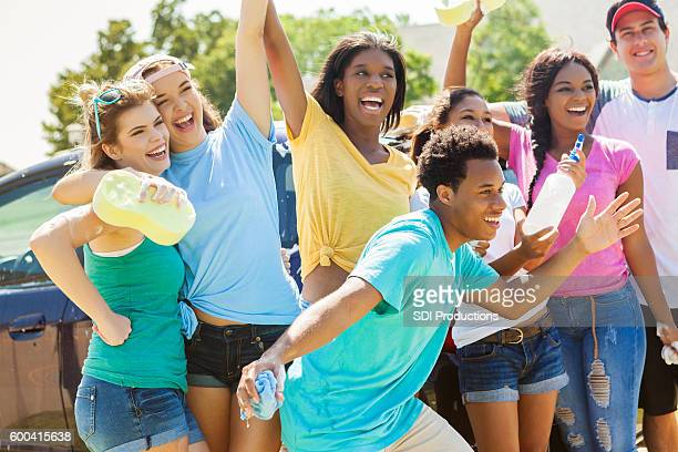 carefree teenage friends enjoy car wash fundraiser - teenagers only stock pictures, royalty-free photos & images