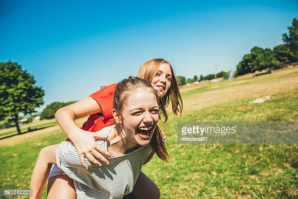 Carefree teenage girl carrying friend piggyback in park