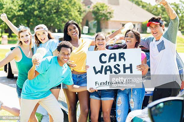 carefree teenagers organize charity car wash - charity benefit stock pictures, royalty-free photos & images