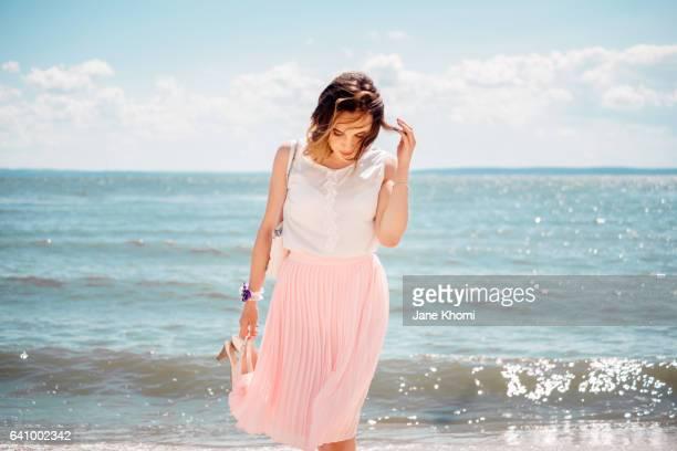carefree woman at beach - jupe vent photos et images de collection