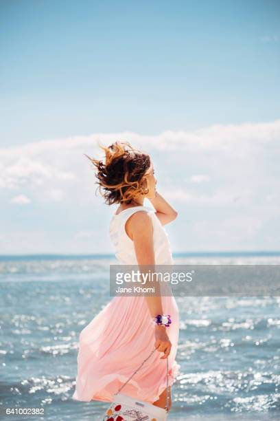carefree woman at beach - skirt blowing stock photos and pictures