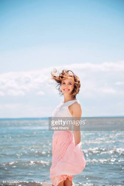 carefree woman at beach - wind blowing up skirts stock photos and pictures