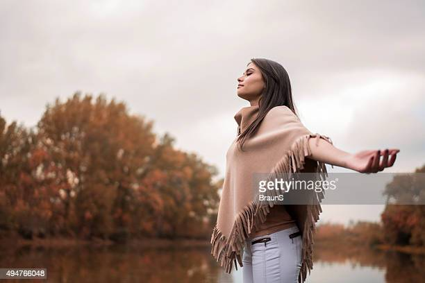 Carefree woman breathing fresh autumn air near the river.