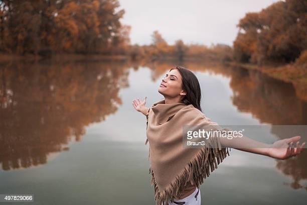 Entspannte Frau Atmen frischen Luft der Herbst nahe dem Fluss.