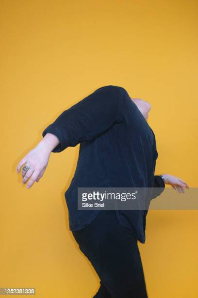 carefree woman dancing against yellow background - briel stock pictures, royalty-free photos & images