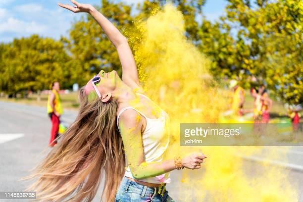 sorgfri kvinna dansar i puder på holi festivalen - flying solo after party bildbanksfoton och bilder