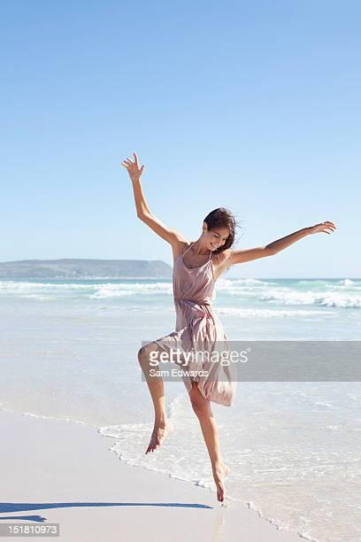 carefree woman dancing on sunny beach - só uma mulher jovem imagens e fotografias de stock