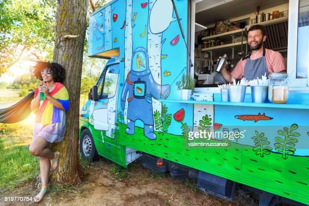 Sans soucis femme buvant cocktail devant le camion de nourriture