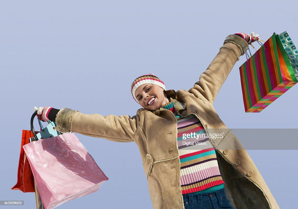 Carefree Woman in Winter Clothing Holding Out Shopping Bags : Stock Photo