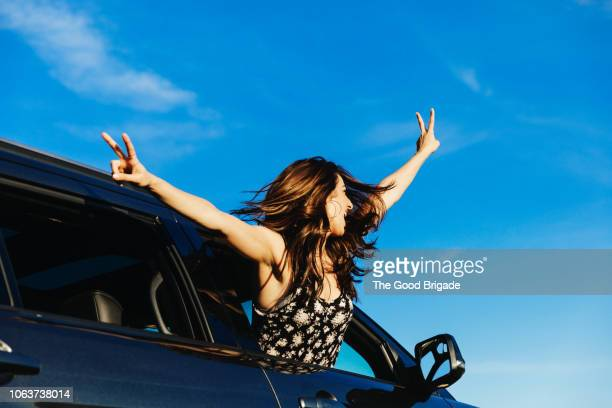 carefree woman leaning out from car window with arms outstretched - tousled hair stock pictures, royalty-free photos & images