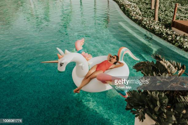 carefree woman on inflatable unicorn - piscina foto e immagini stock