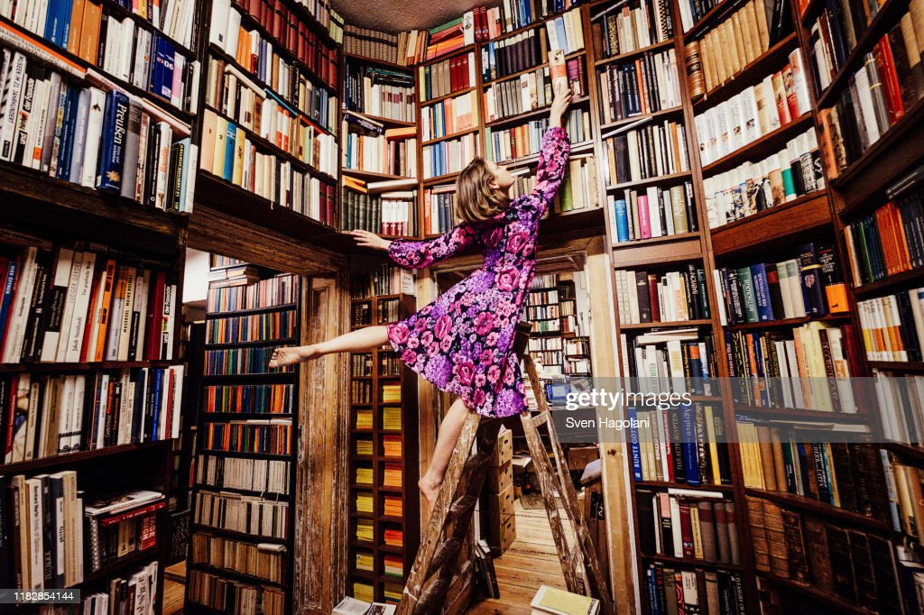 Carefree woman on ladder reaching for book in library : Stockfoto
