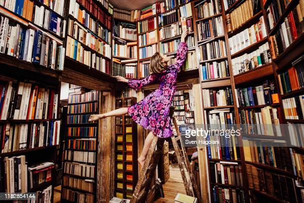 carefree woman on ladder reaching for book in library - library stock pictures, royalty-free photos & images
